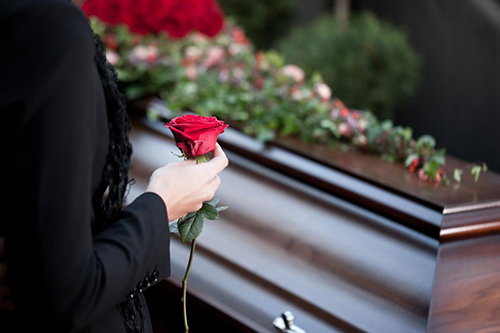 woman holding rose in front of a casket